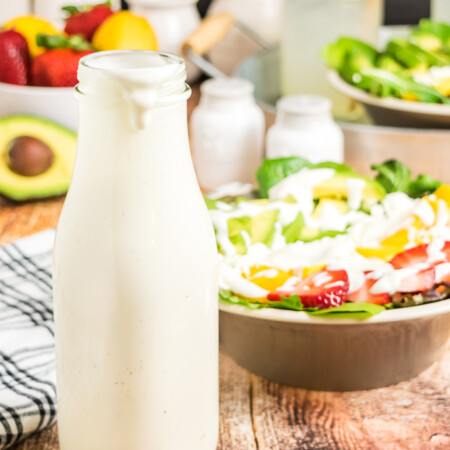 Creamy Greek Yogurt Honey Lemon-Lime Dressing in a bottle with a salad in the background
