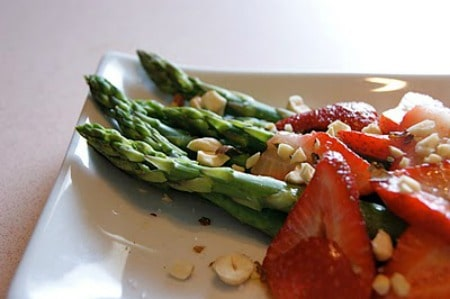 Asparagus with White Balsamic, Fresh Strawberries and Hazelnuts on a plate