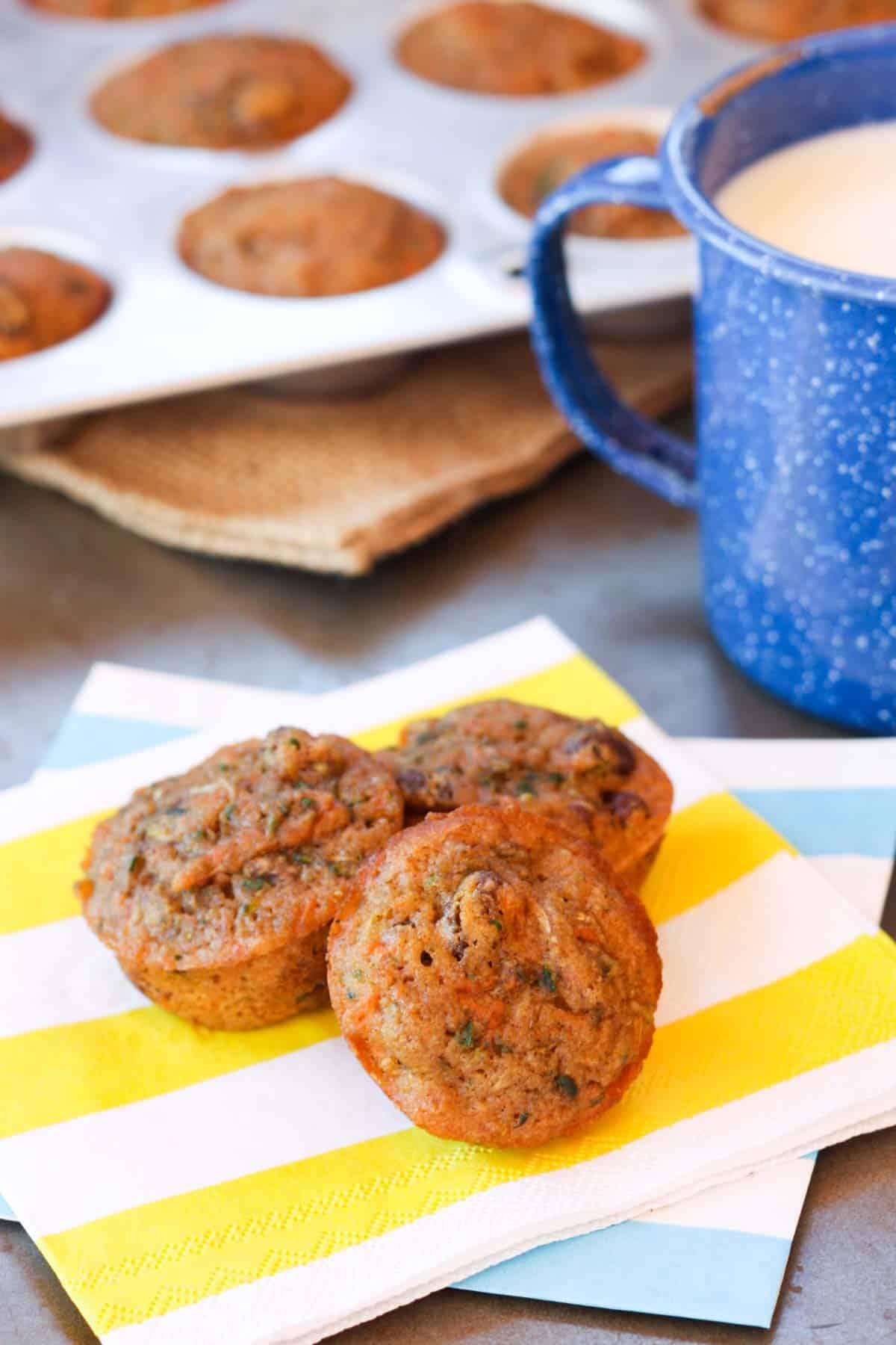 three muffins on a stack of two colored napkins in front of a mini muffin tin