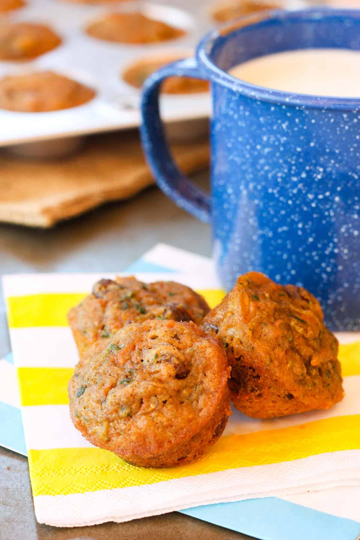 Healthy Carrot Zucchini Muffins on a striped napkin next to a blue speckled mug of milk