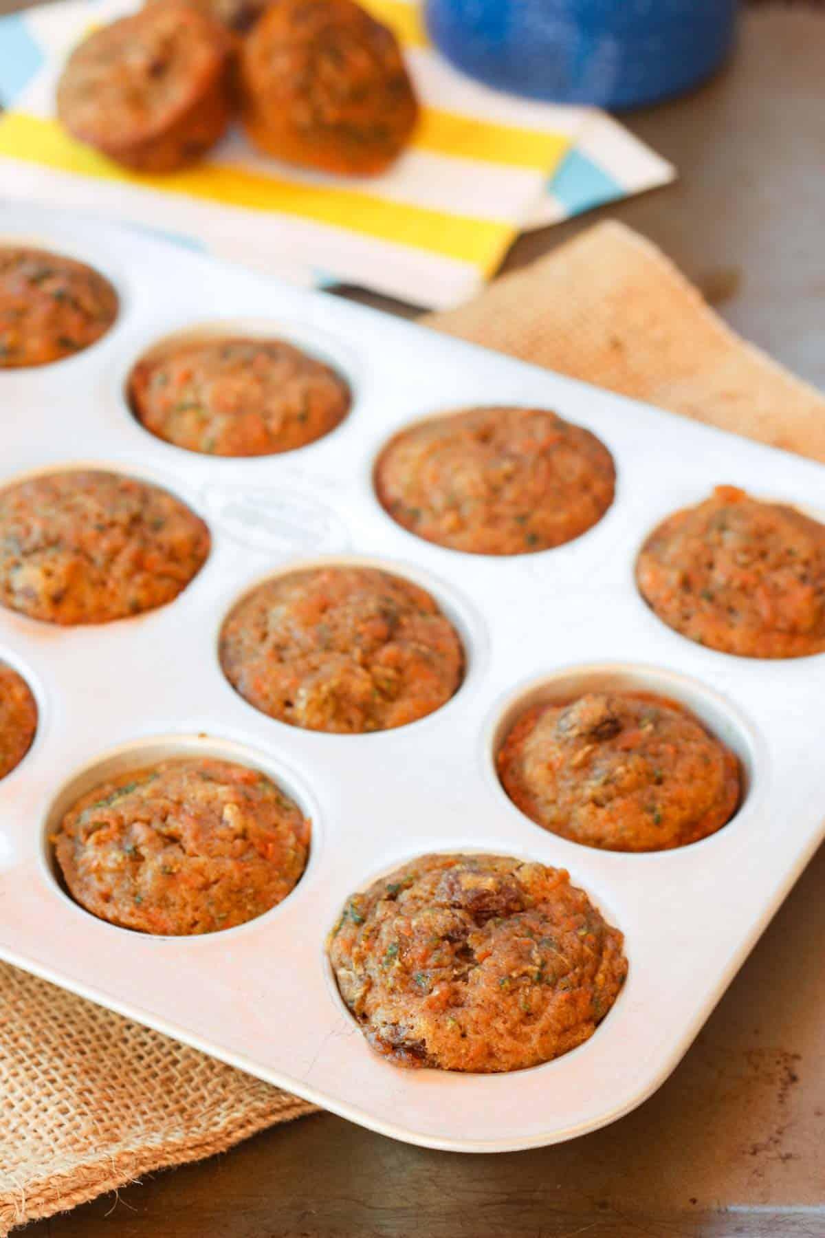 A mini muffin tin filled with zucchini carrot muffins