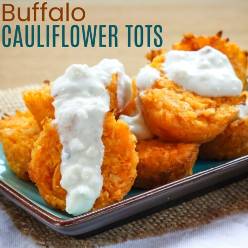 Buffalo cauliflower tots on a turquoise plate with blue cheese dressing on top