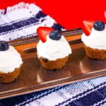 Three Cheesecake Chocolate Chip Cookie Cups topped with berries on a rectangular silver platter