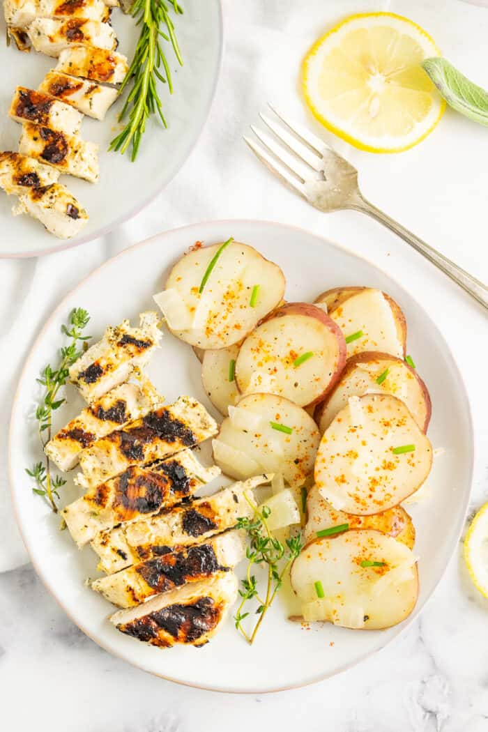 Grilled chicken dinner on a plate with cooked potato slices