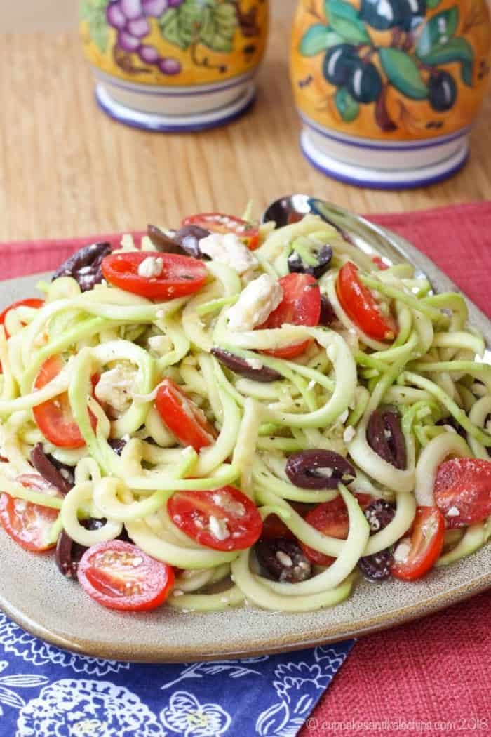 zoodles greek salad piled on a plate