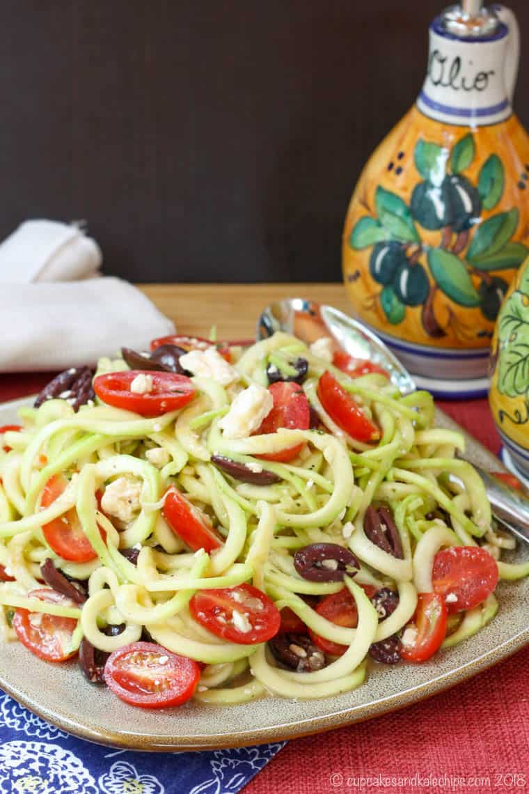 Greek Zoodle Salad on a plate with a black background
