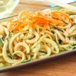 Cold Sesame Peanut Zucchini Noodles Salad topped with shredded carrots and sesame seeds on a green plate