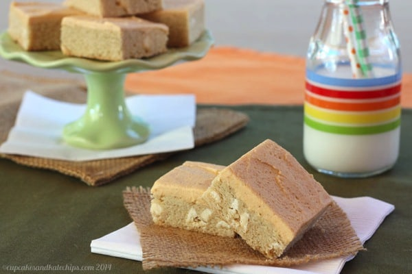 Frosted sugar cookie bars in the foreground, served next to a tall glass of milk