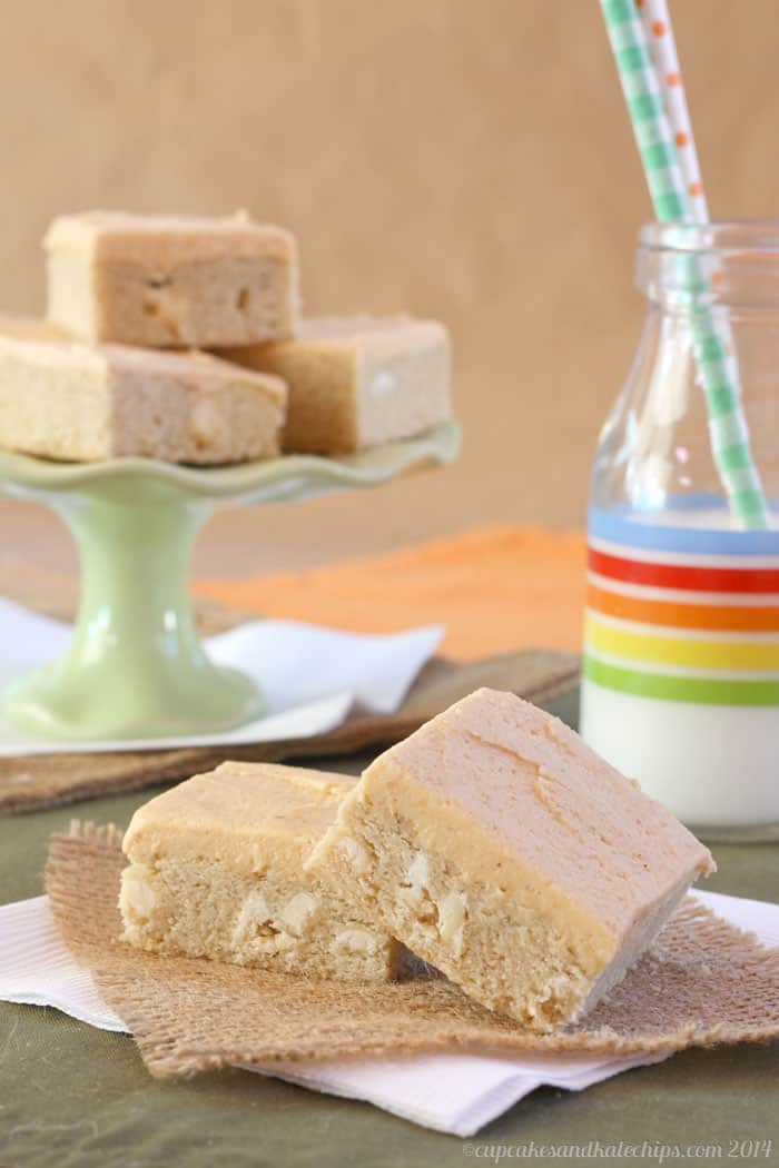 White Chocolate Chip Sugar Cookie Bars with Pumpkin Spice Frosting on a napkin with more on a cake pedestal