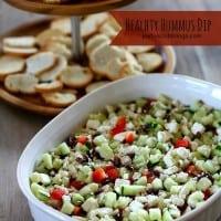 layered greek humus dip in a white ceramic dish