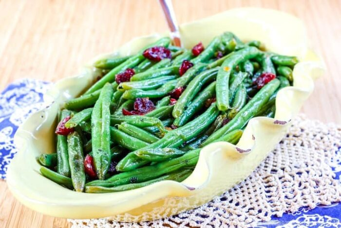 Cranberry Orange Glazed Green Beans in a yellow serving dish