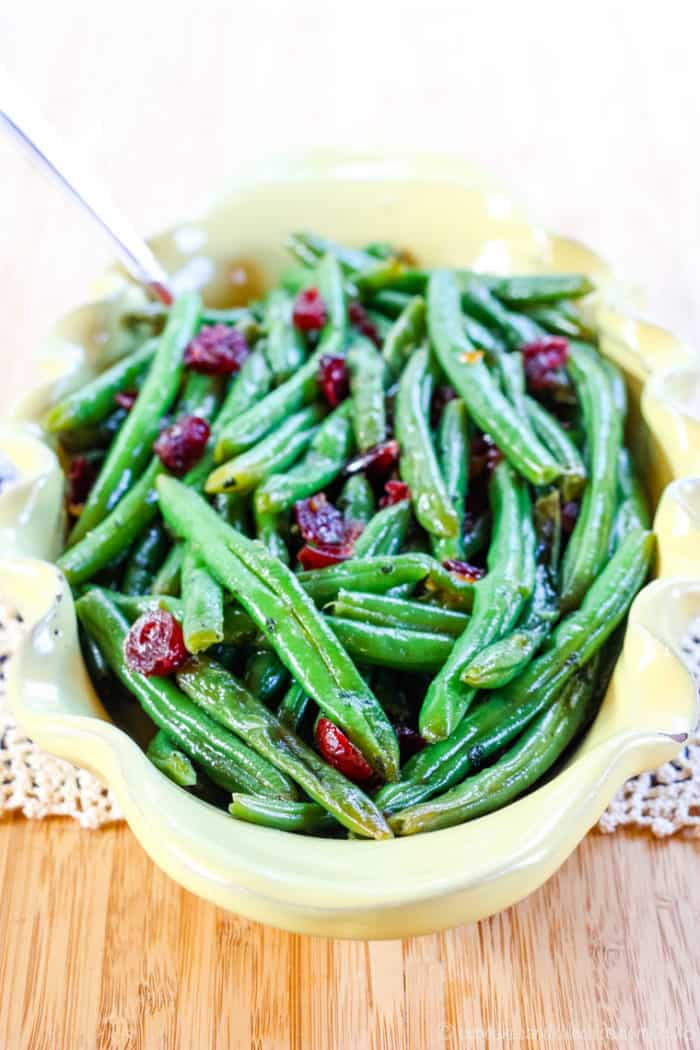Easy green beans recipe with dried cranberries and orange glaze in a yellow serving dish