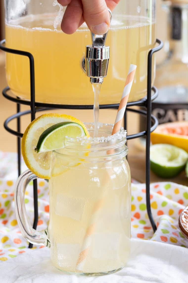 Light Grapefruit Margarita in a pitcher filling a glass with this cocktail recipe