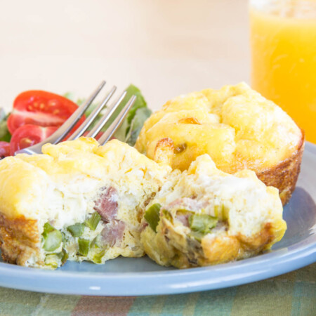 Asparagus and ham egg muffins served with a glass of orange juice