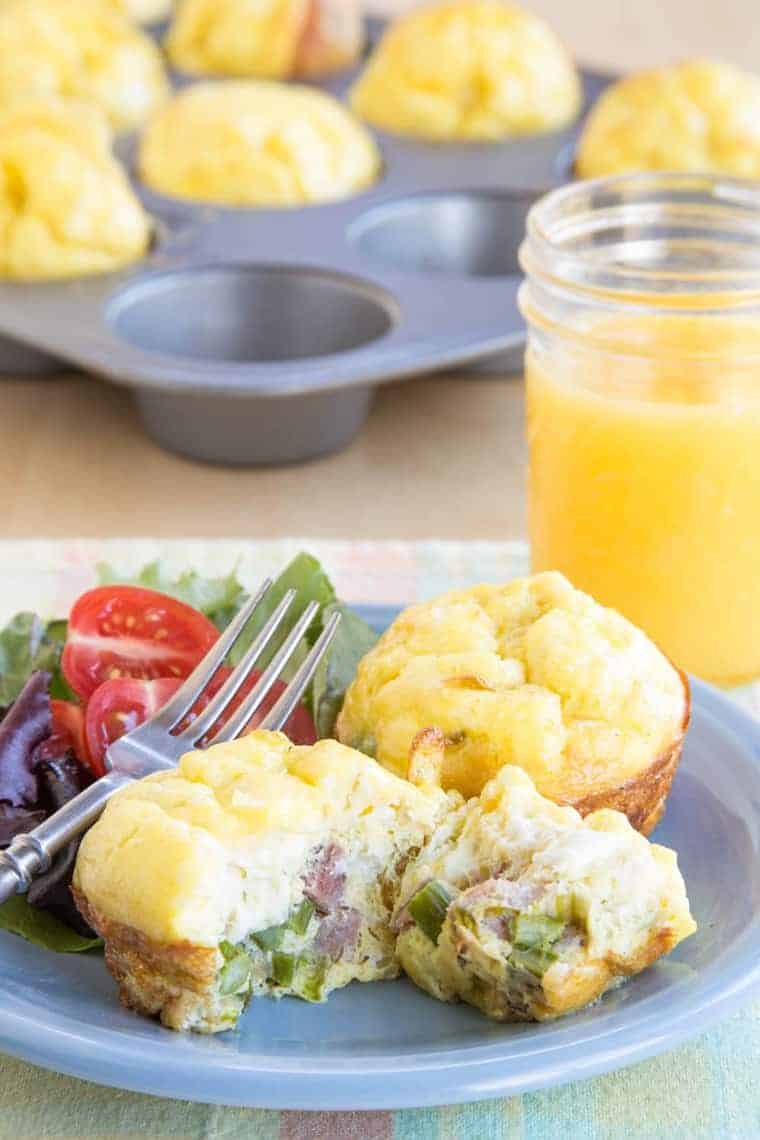 Asparagus ham egg muffins on a plate with a salad and the rest in a muffin tin