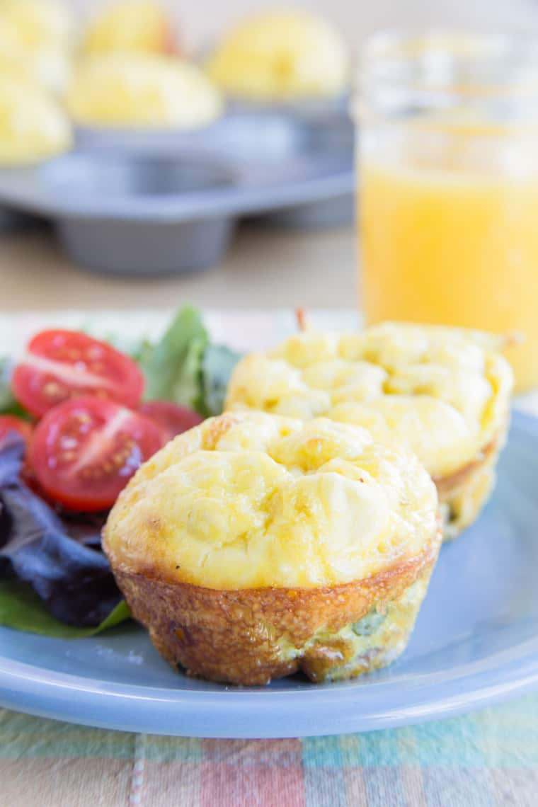 Two whole egg muffins on a plate with a side salad