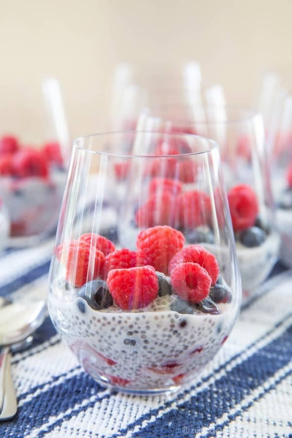 A single glass with a Triple Berry Coconut Chia Seed Parfait and more parfaits in the background