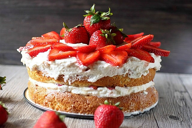 Two-layered Strawberry Tres Leche Cake with frosting and fresh strawberries