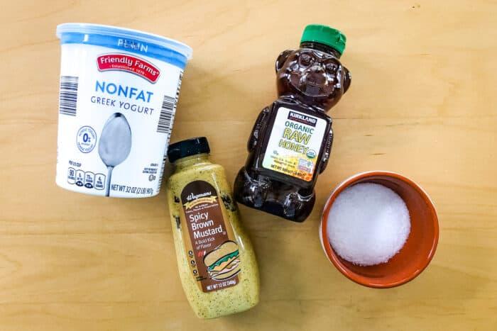 containers of plain Greek yogurt, spicy brown mustard, honey, and salt
