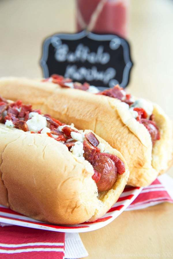 Closeup of Buffalo, Bacon, and Blue Cheese Hot Dogs in a bun on a red and white striped plate