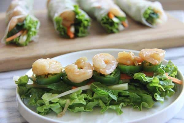 Preparing Shrimp Rice Paper Rolls with shrimp and veggies on a plate