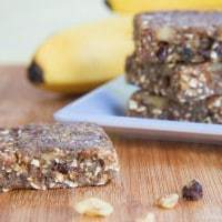 Banana Nut Energy Bars stacked on a plate with one on a cutting boars with scattered walnuts and chocolate chips