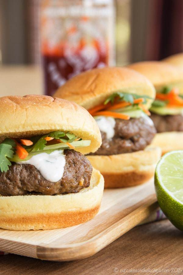 Mini Thai Burgers topped with cucumbers, carrots, and cilantro lime cream on a wooden platter