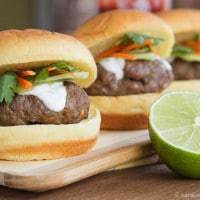 A row of Thai Sliders on a wooden platter