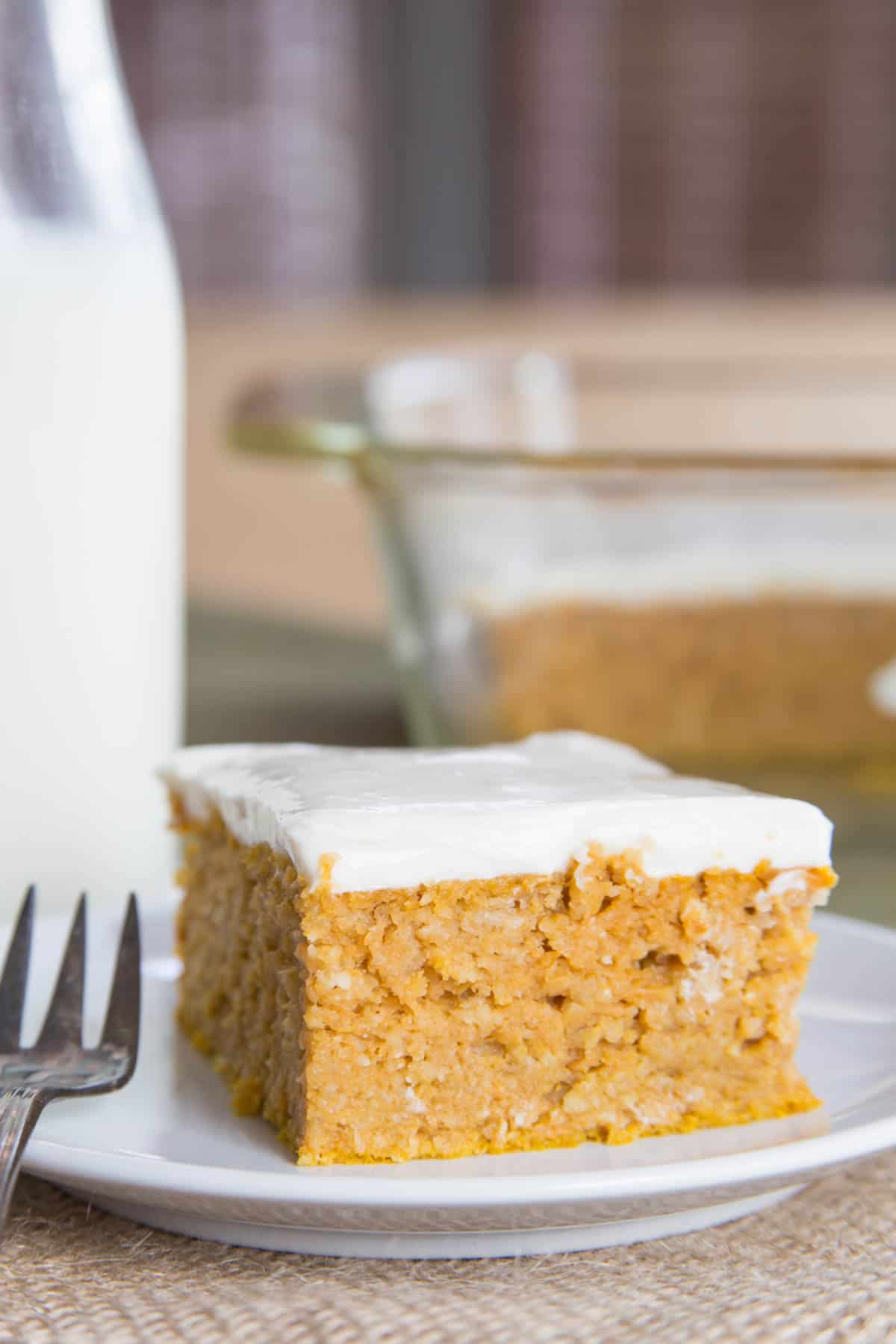 A square slice of baked pumpkin snack cake on a plate