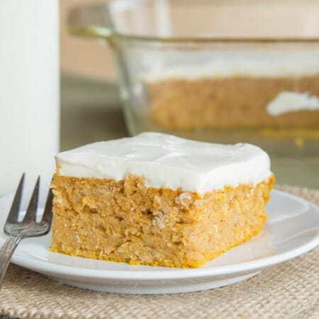 Healthy snack cake being served on a white plate in front of the rest of the cake in a glass baking pan