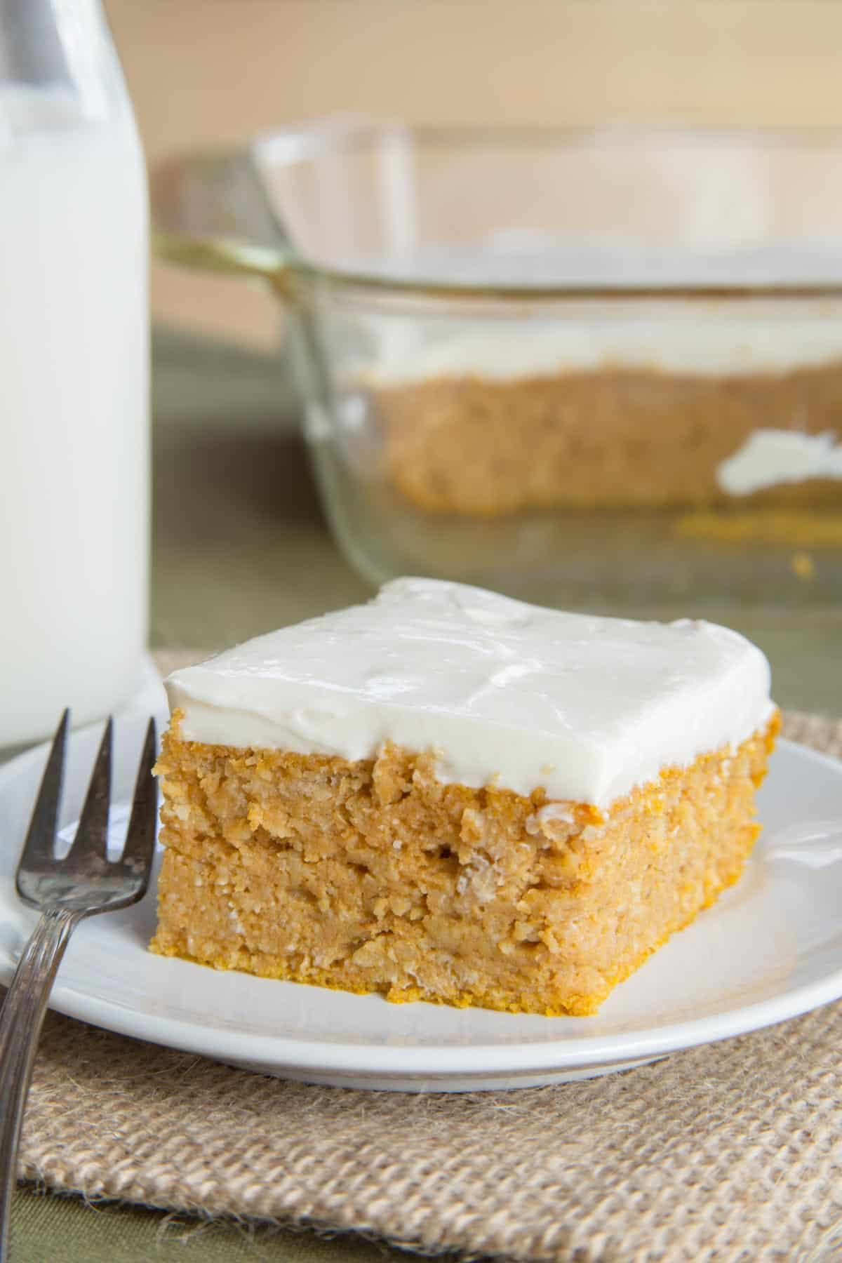 Pumpkin Snack Cake served with Greek Yogurt Cream Cheese Frosting on a white plate with a small dessert fork