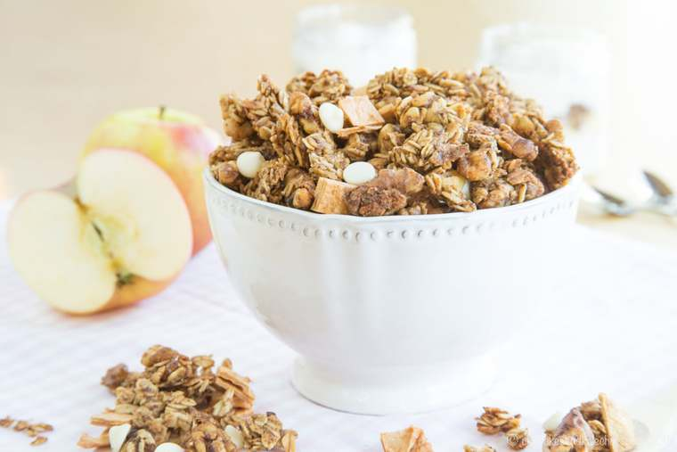Apple Cinnamon Granola with nuts in a bowl with apples and yogurt parfaits in the background