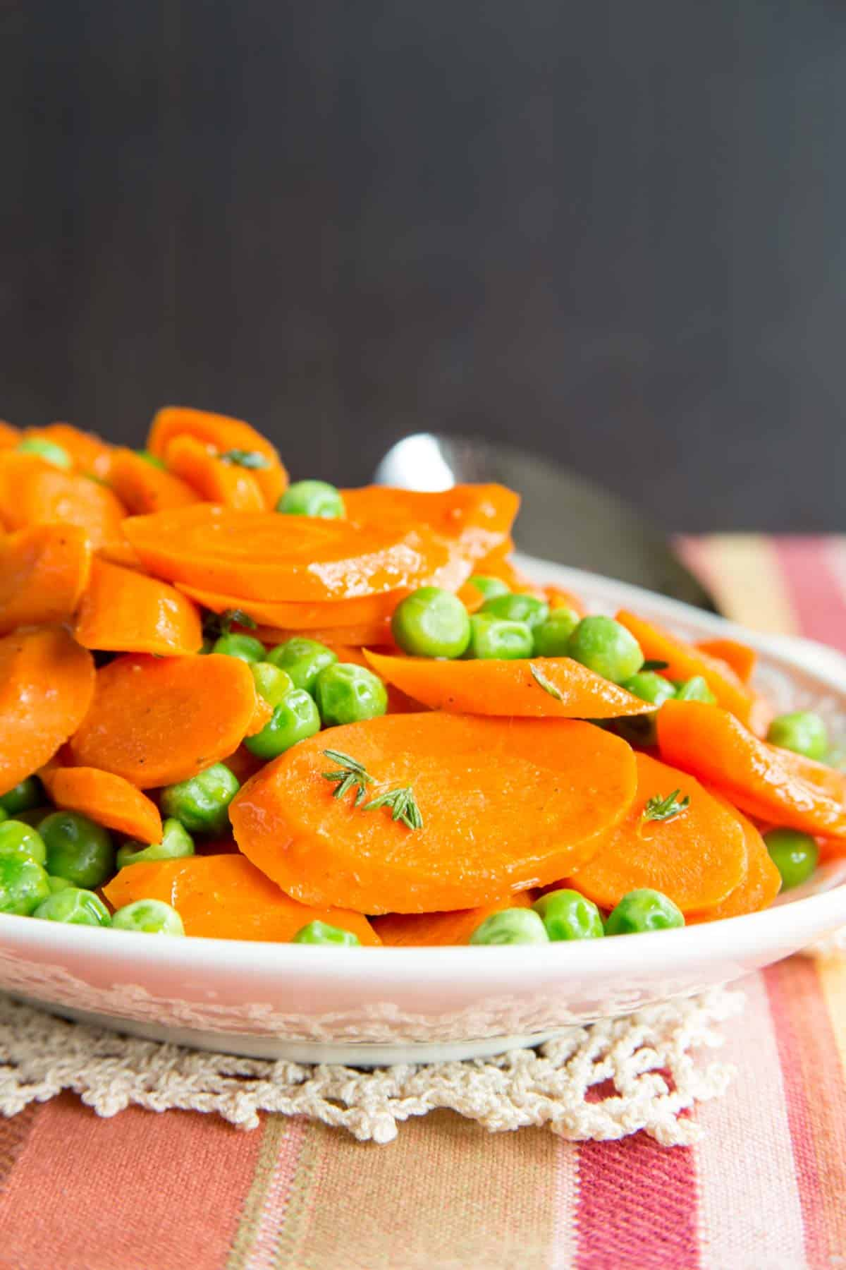 Closeup of browned butter peas and carrots with a black background