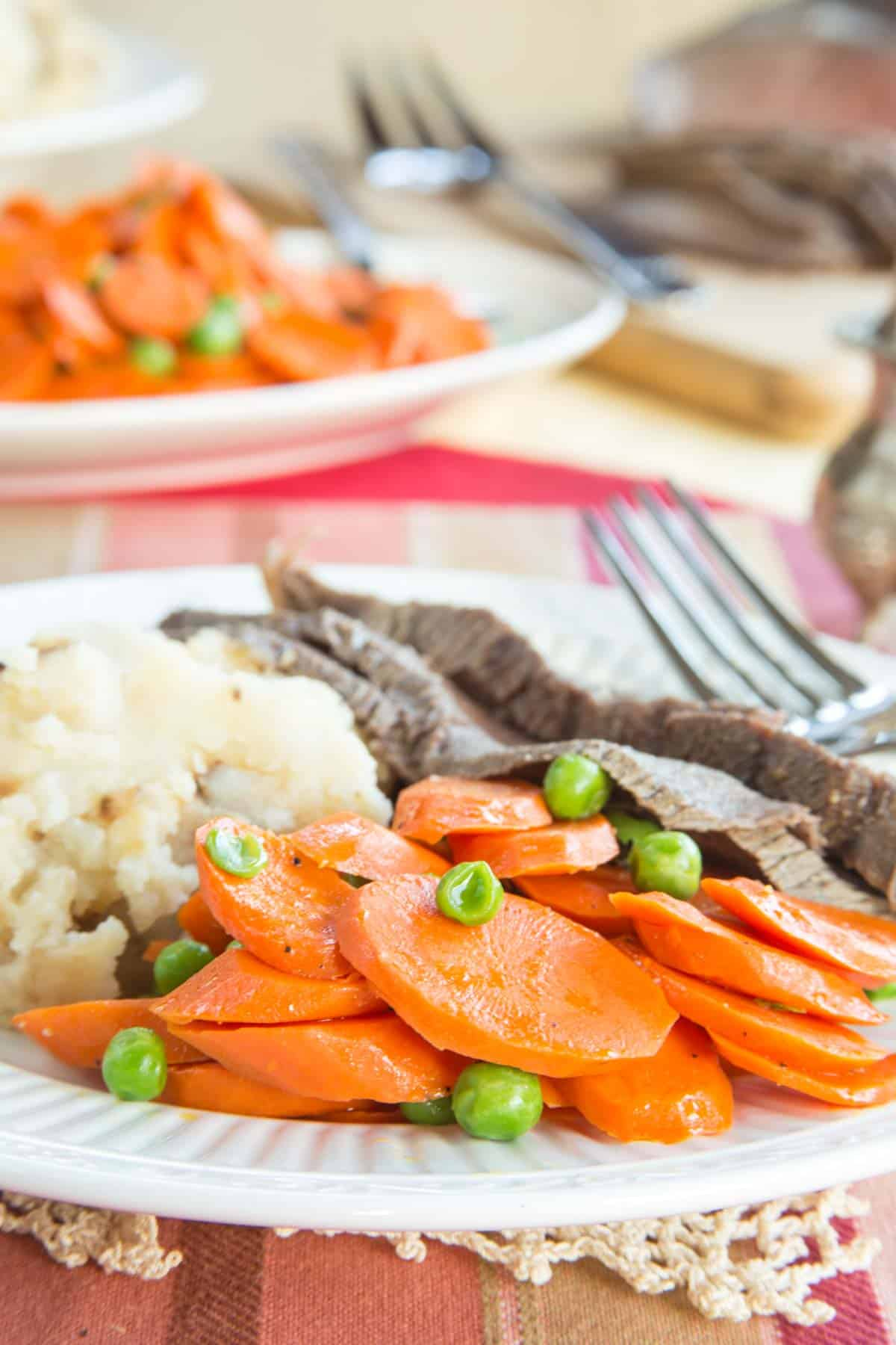 Brown Buttered Peas and Carrots on a plate with steak and mashed potatoes