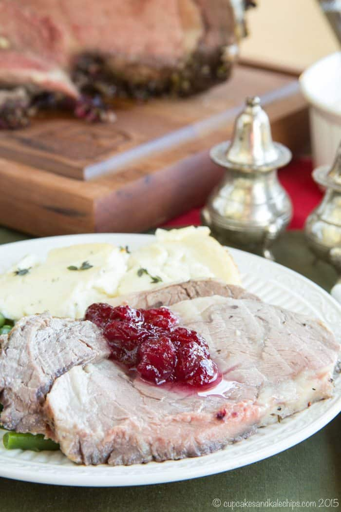 Slices of Cranberry Crusted Prime Rib Roast on a plate topped with cranberry sauce