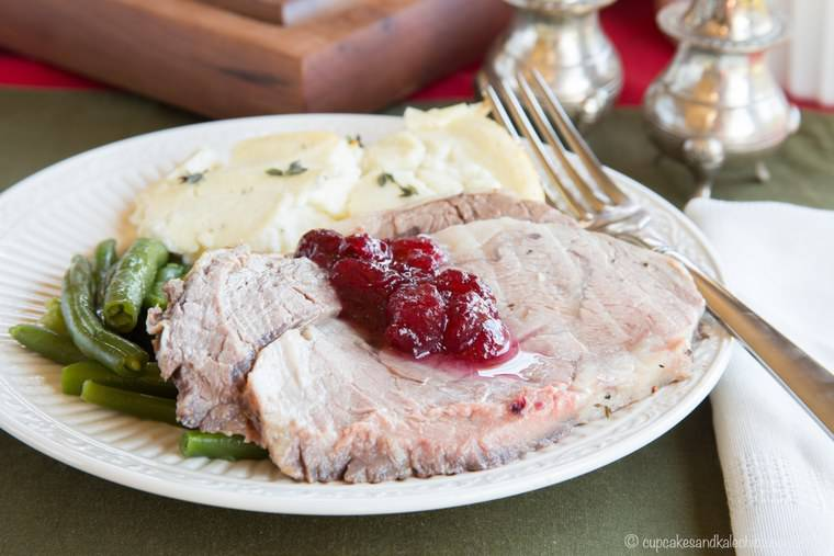 Cranberry Crusted Prime Rib topped with cranberry sauce on a plate with side dishes
