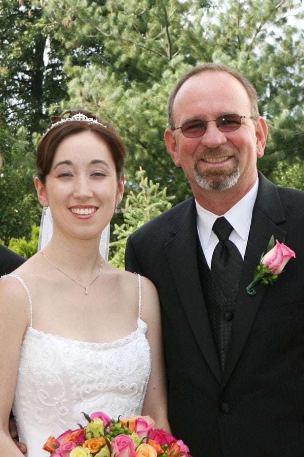 happy bride on her wedding day standing next to her father