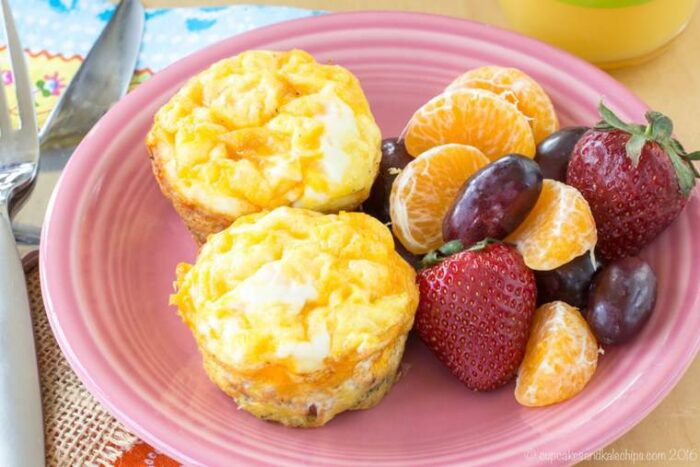 Low Carb Gluten Free Broccoli Ham and Cheese Egg Muffin Cups on a pink plate with fruit