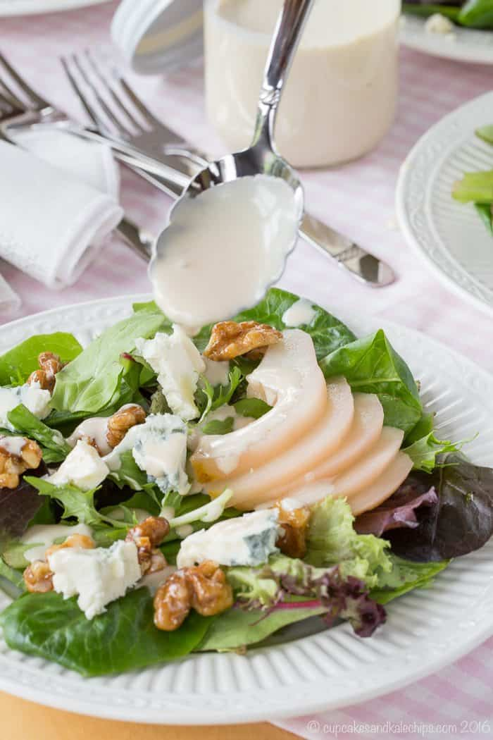 Drizzling creamy sherry dressing onto a salad from a spoon