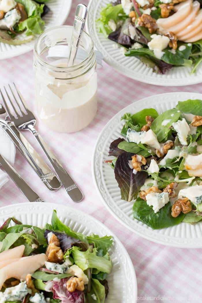 plates of mixed greens with poached pears, glazed walnuts, and blue cheese plus a jar of dressing