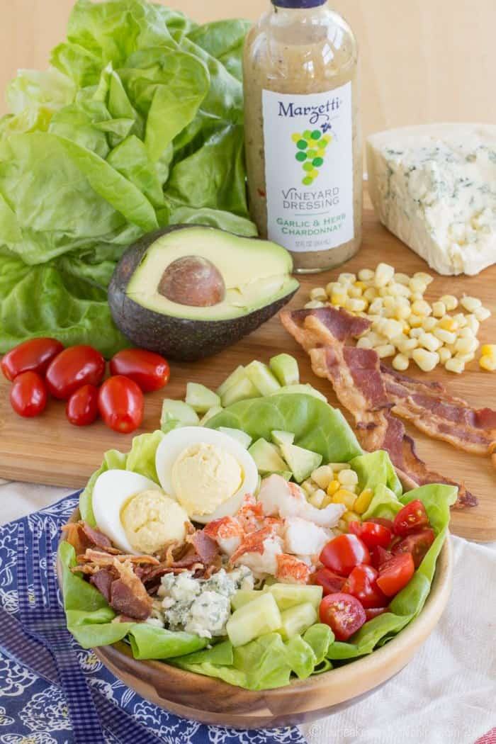 Cobb-Style Lobster Salad with bacon, avocado, corn, and tomatoes on a cutting board