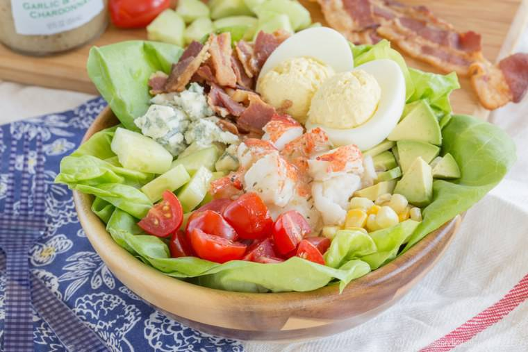 A wooden bowl with Lobster Cobb Salad