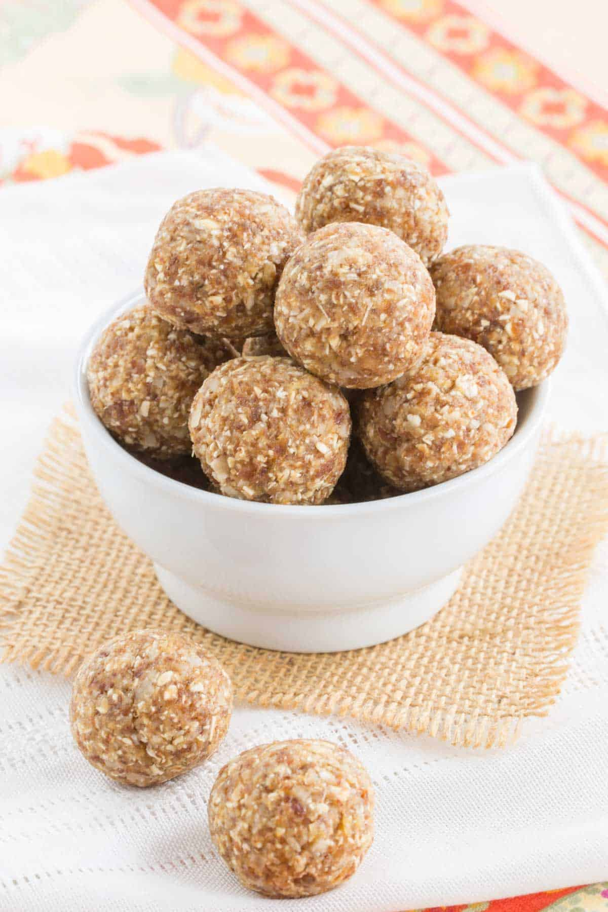 Pineapple coconut energy balls in a small white bowl on a piece of burlap and two more on a cloth napkin