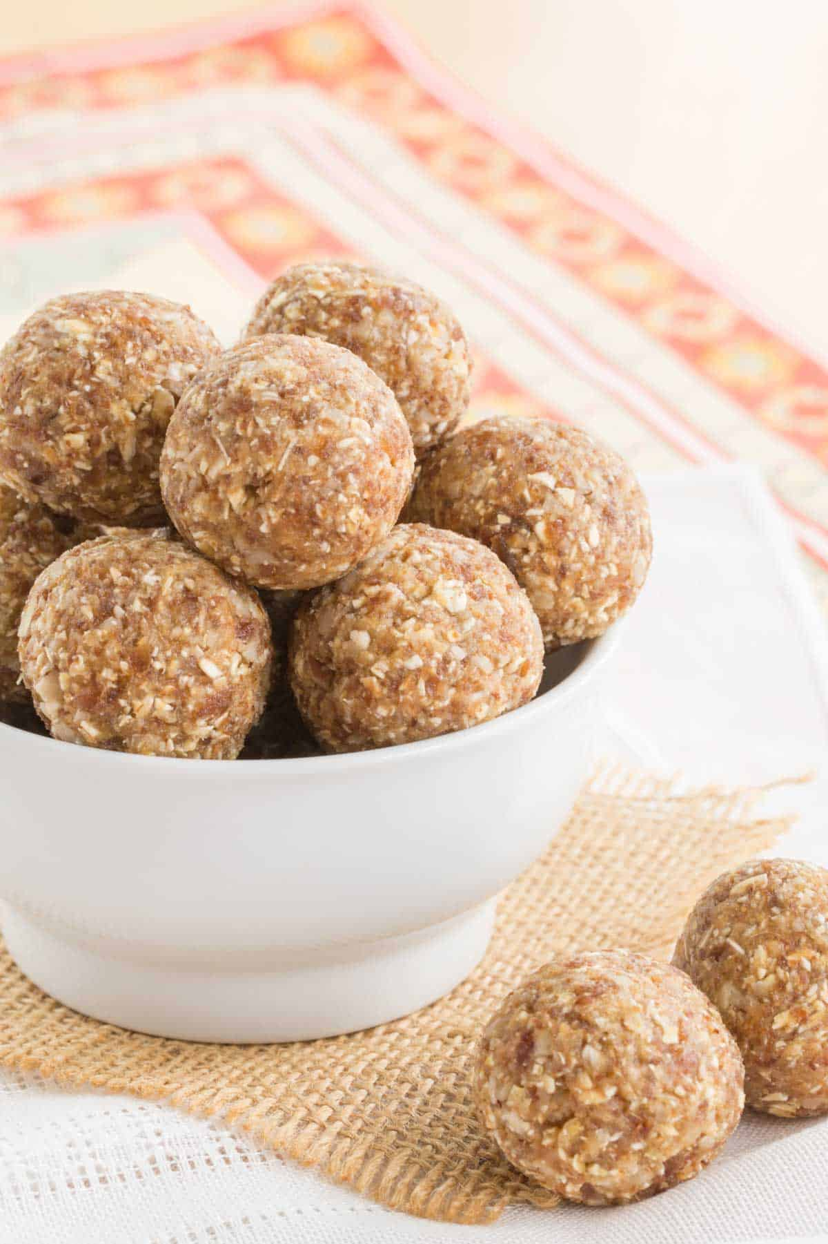 pineapple coconut energy balls in a white bowl with two on a piece of burlap on top of a cloth napkin
