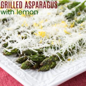 Grilled Asparagus with Lemon and Manchego cheese on a white rectangular plate
