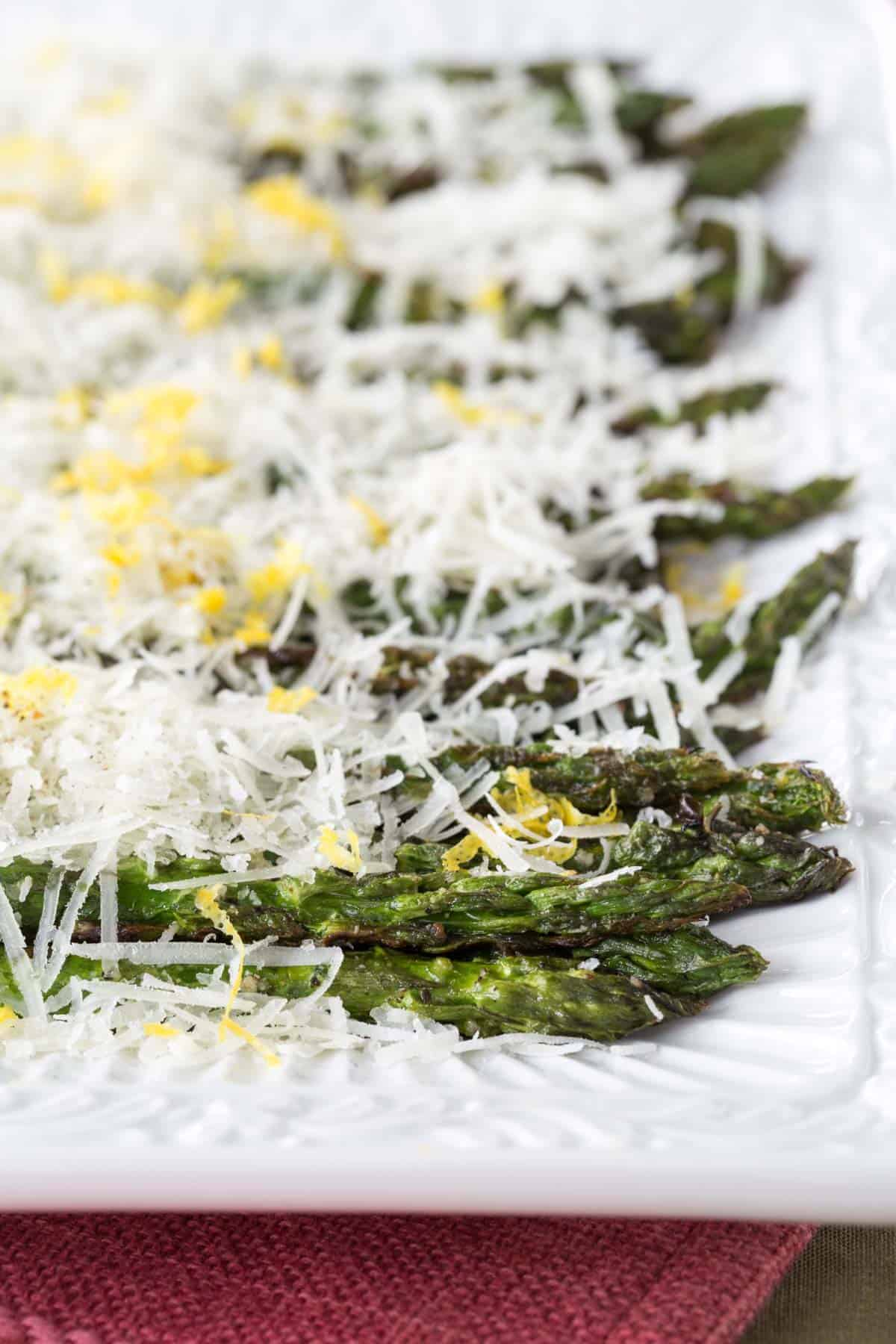 rectangular serving platter with lined up grilled asparagus with cheese and lemon zest