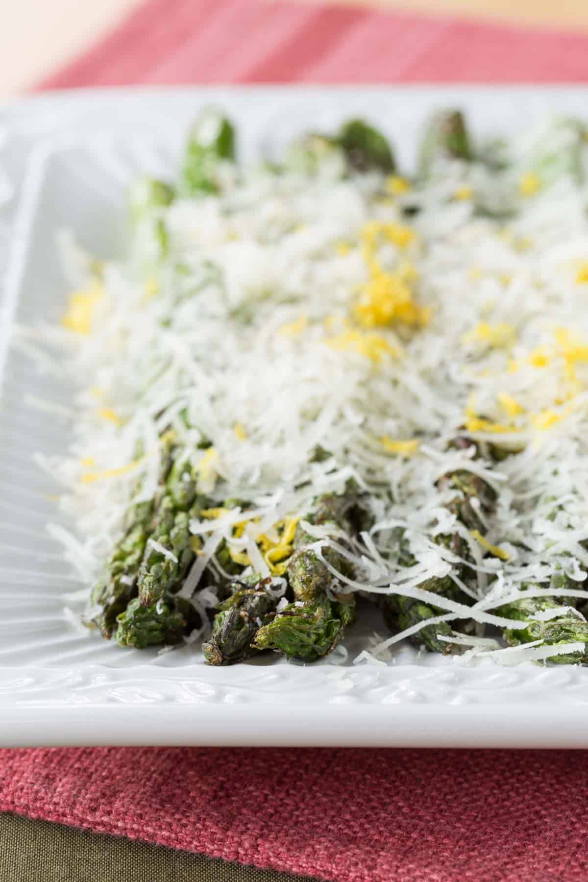 tops of asparagus that has been grilled and topped with lemon zest and finely shredded cheese
