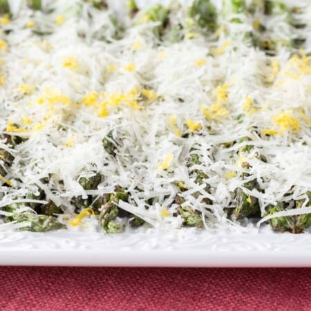 Grilled Asparagus with Lemon and Manchego Cheese laying horizontal on a plate