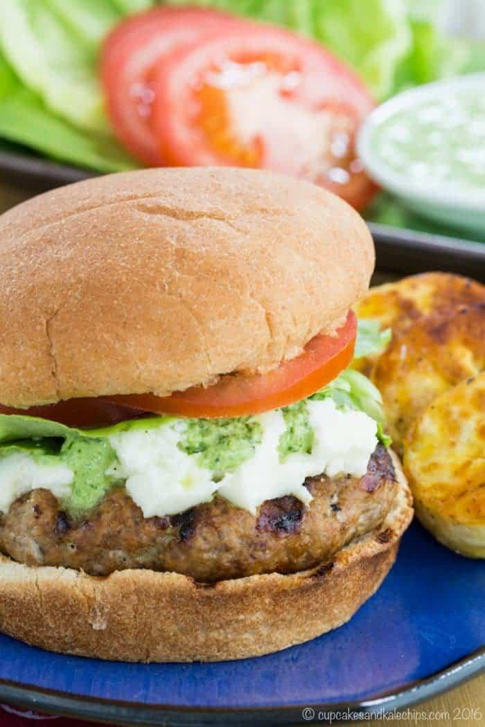 turkey burger on a bun with cheese, lettuce, tomato, and peruvian aji sauce