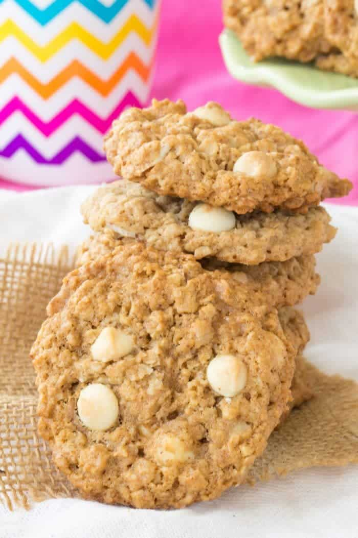 fourn white chocolate chip monster cookies in a stack with one leaning against the pile